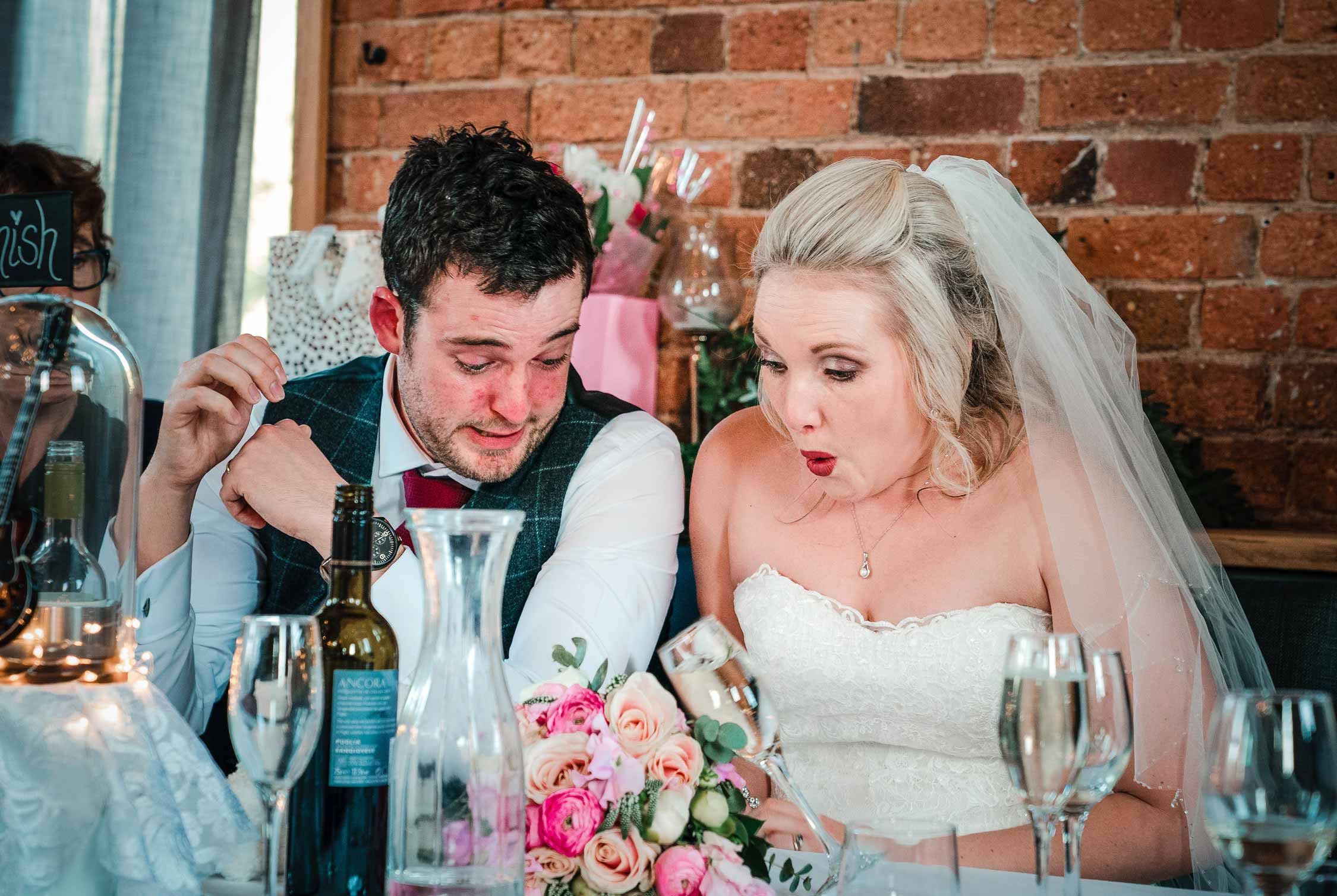 shocked look on bride & groom's face as she knocks over a glass of wine