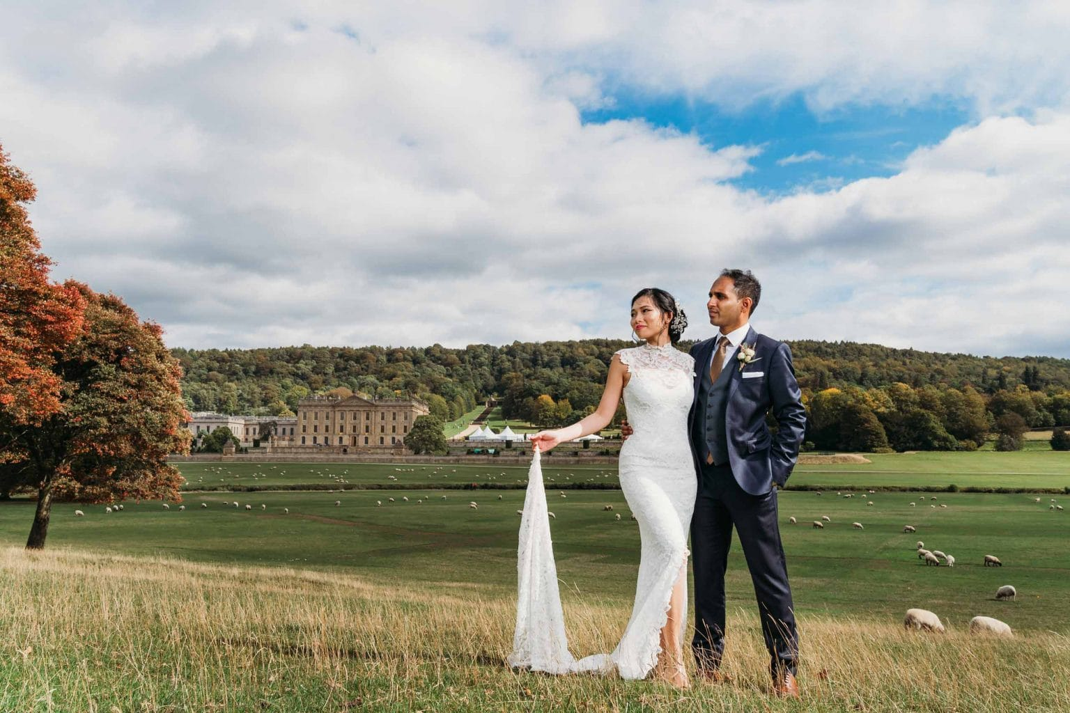 Bride & groom stood outside Chatsworth House with Sheep behind them