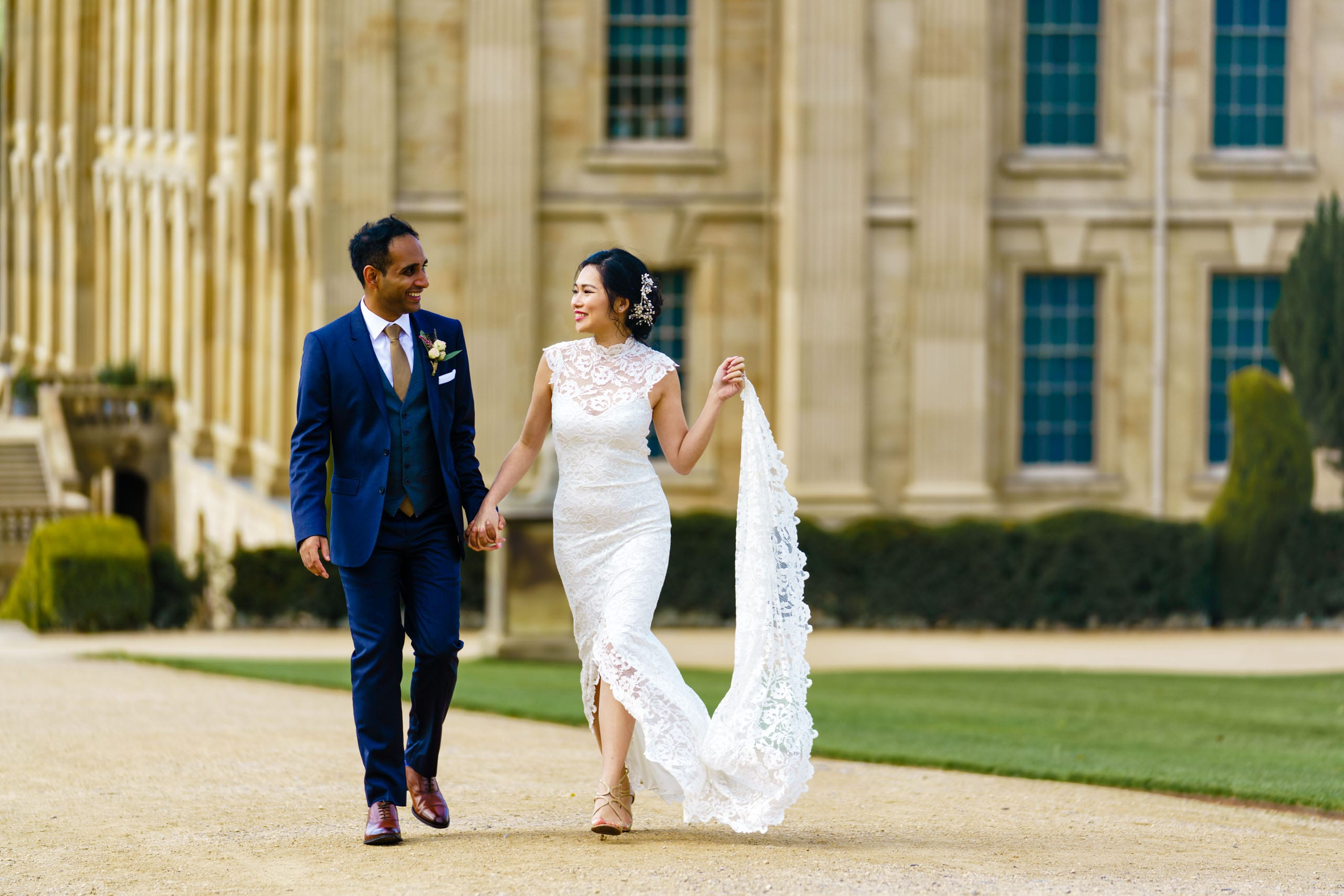 Newlywed Bride & Groom walking hand in hand with Chatsworth House behind them