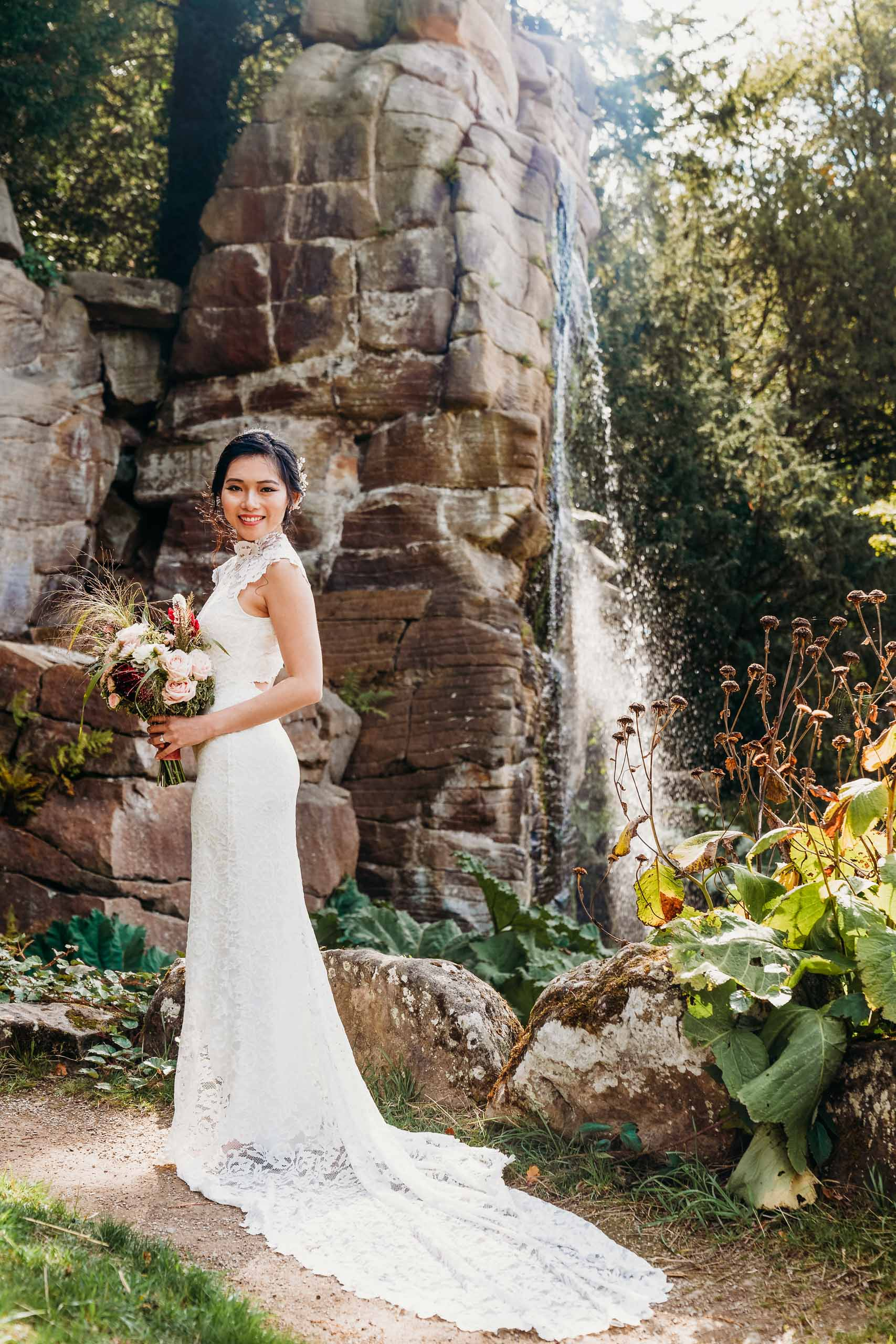 Beautiful Bride stood at waterfall near Chatsworth House gardens