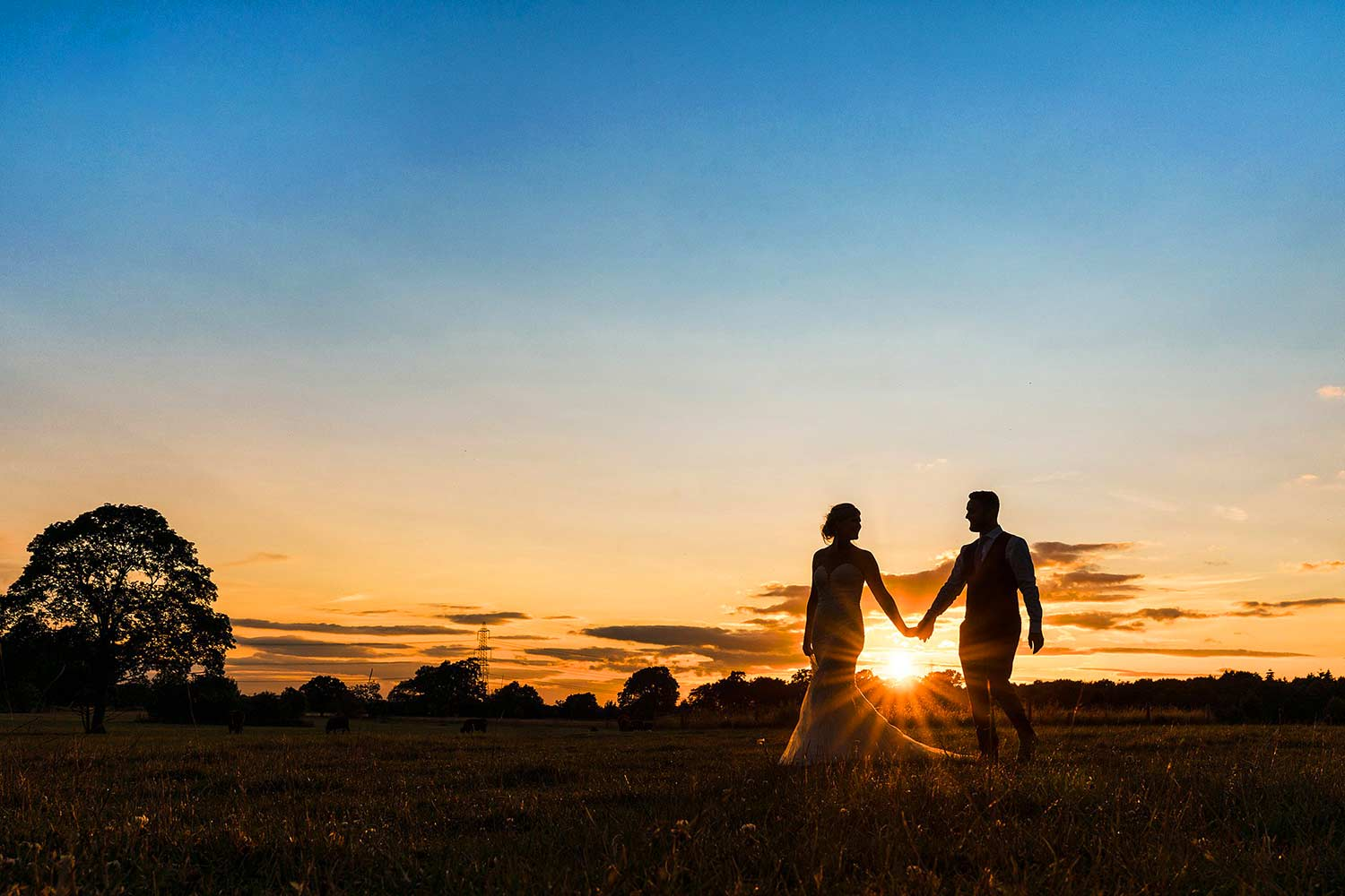 Bride and groom walking hand in hand with the sunset directly behind them