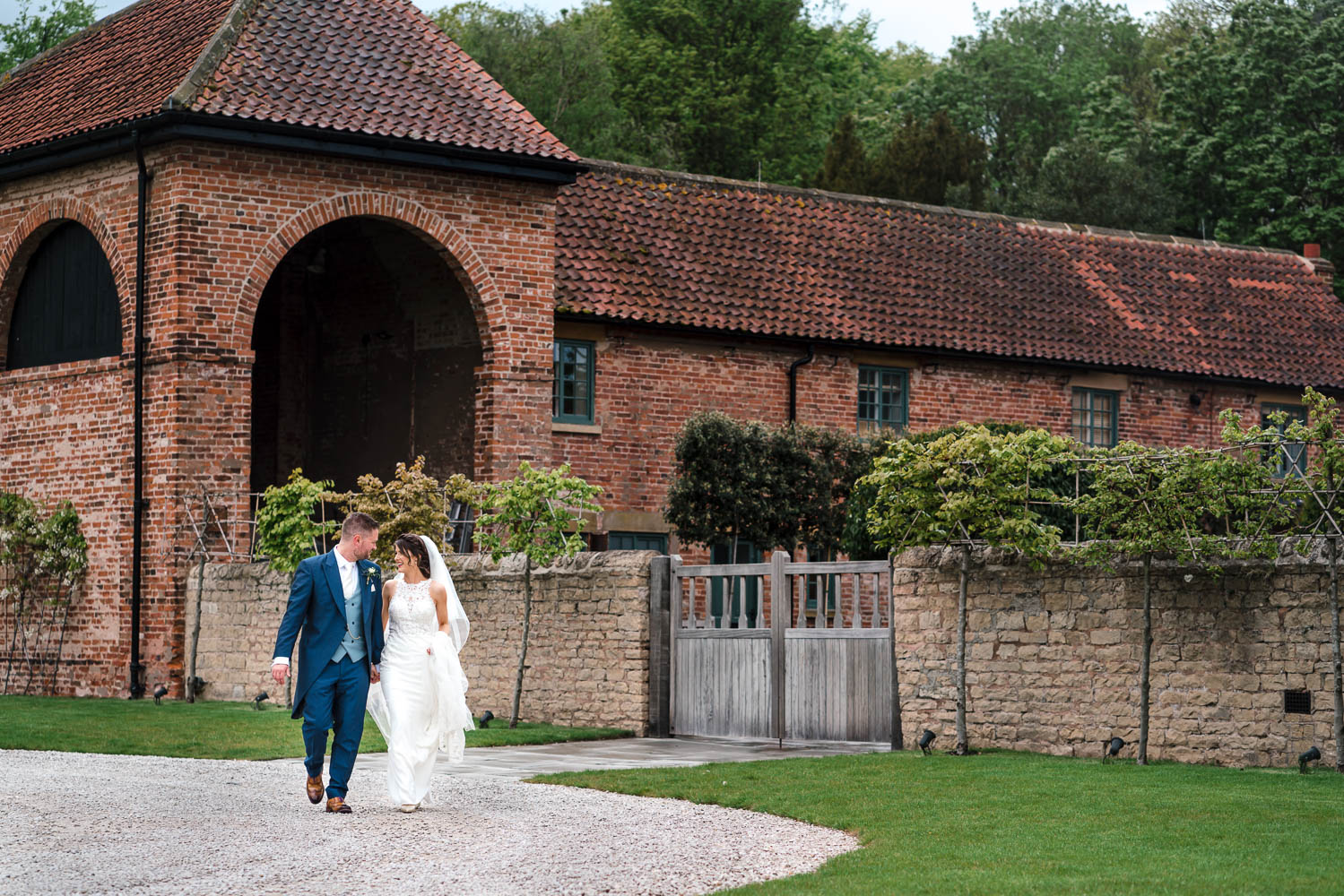 Bride & groom walking outside Hazel Gap Barn - Exclusive wedding venue in Nottinghamshire