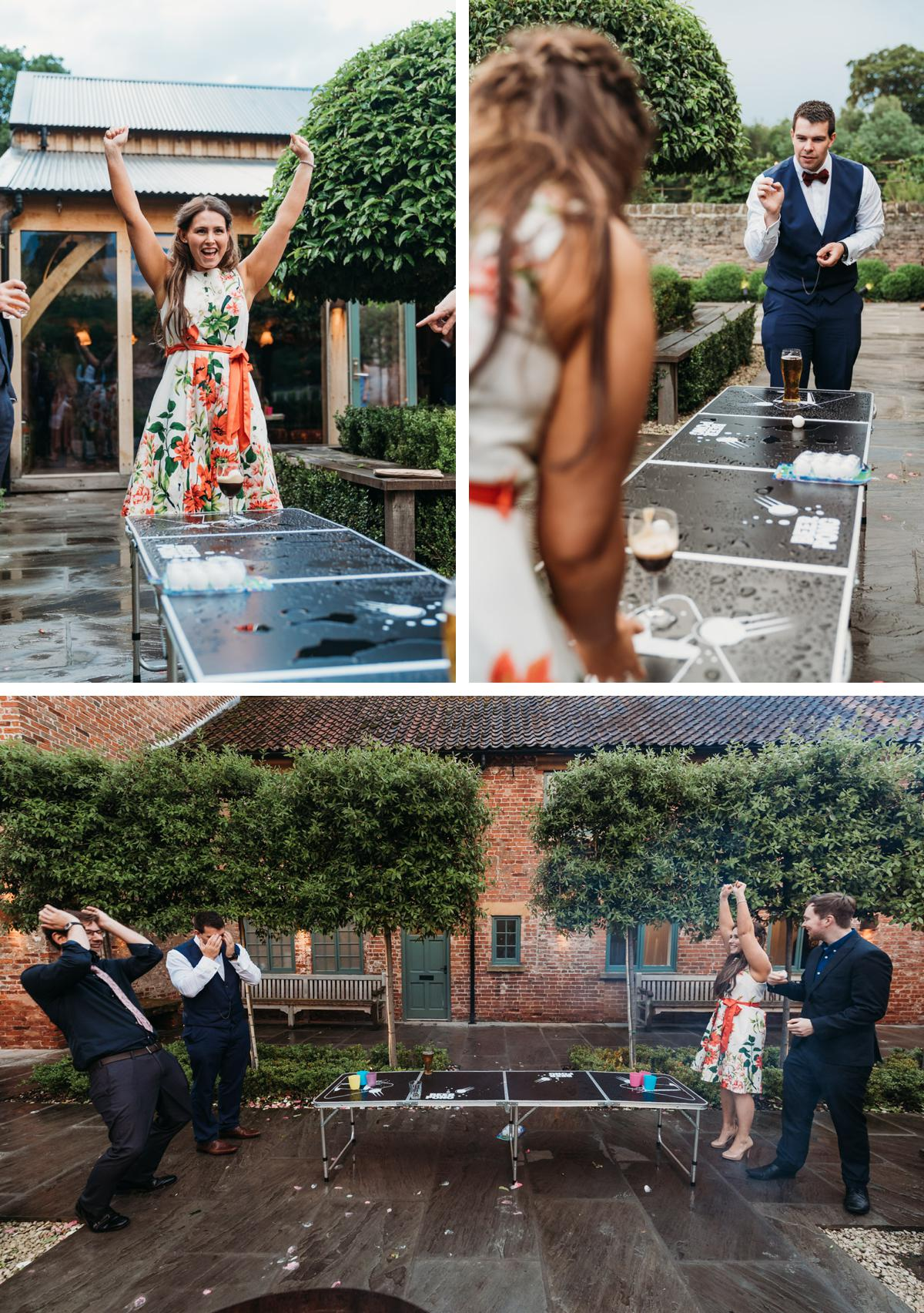 Wedding guests playing beer pong in the courtyard at a Hazel Gap Barn wedding