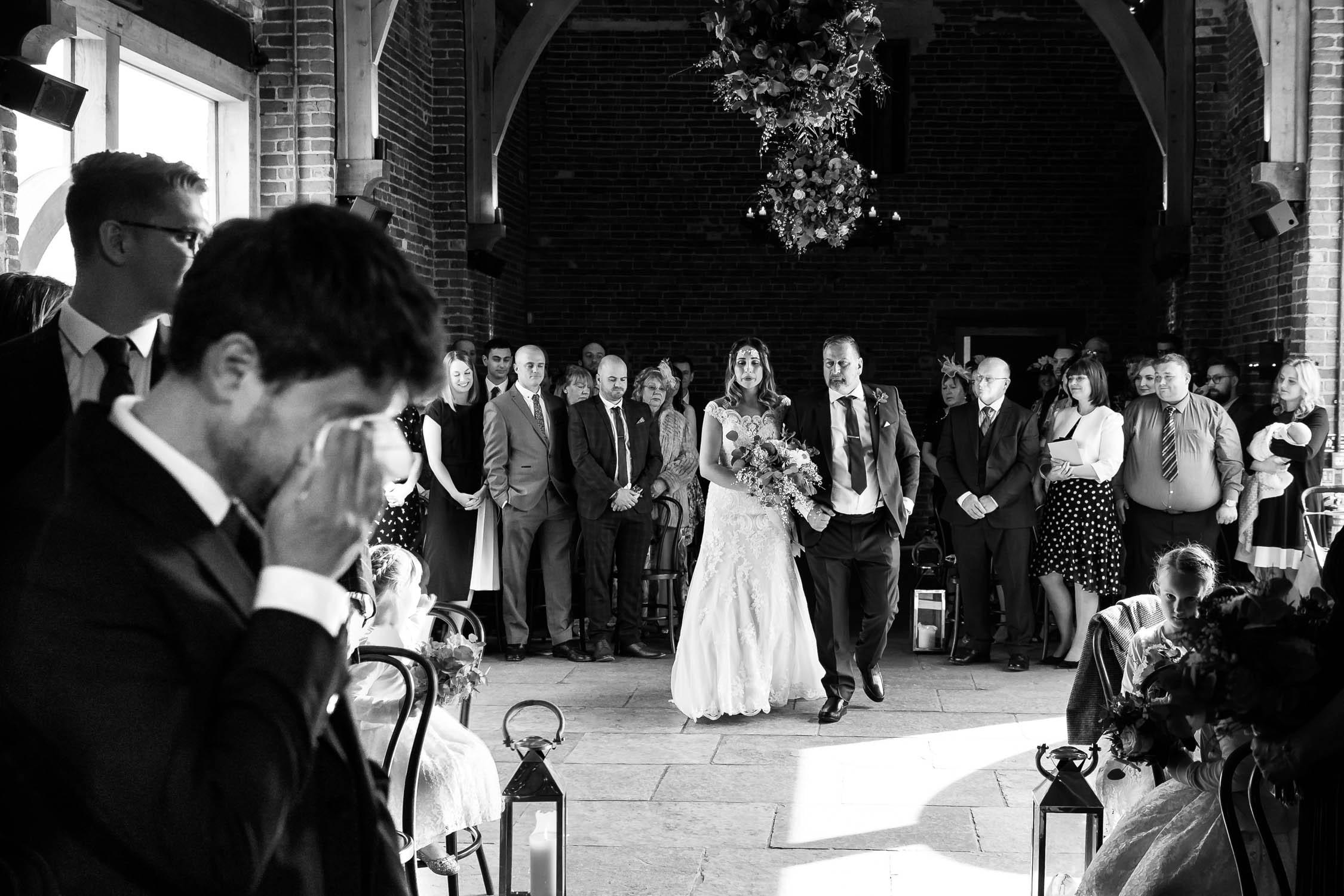 Bride walking down the aisle at Hazel Gap Barn as groom wipes away a tear