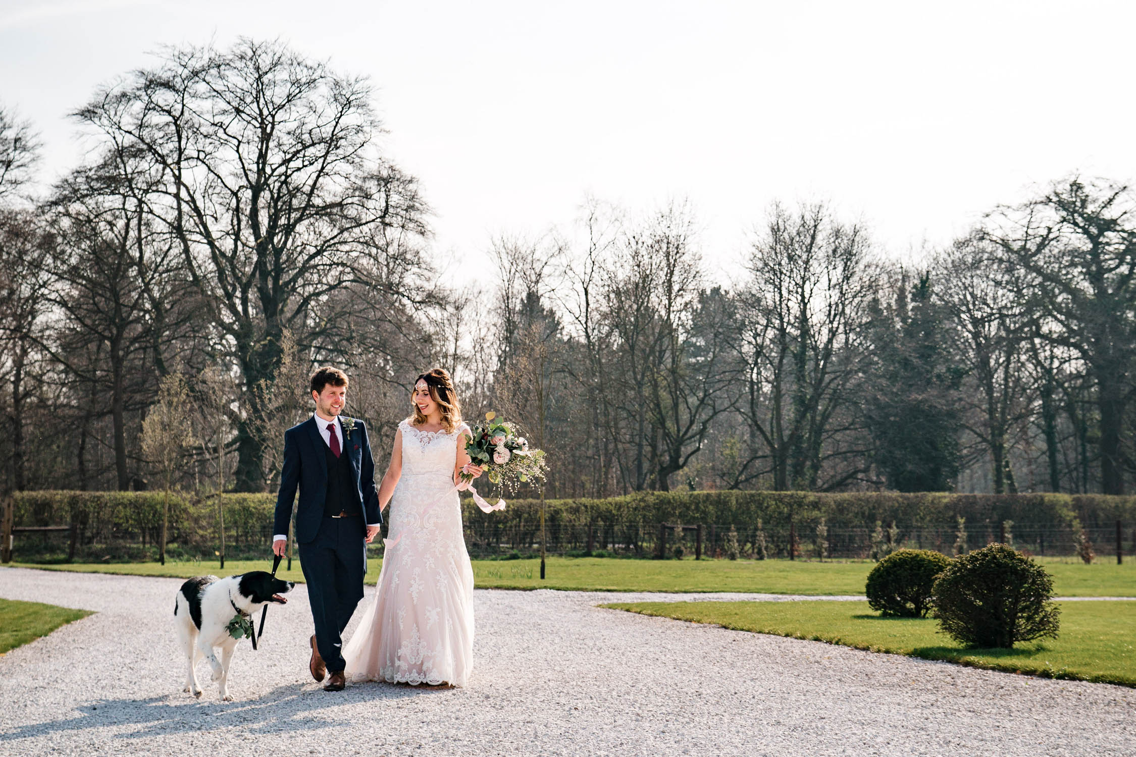 Bride and groom take their dog for a quick walk outside Hazel Gap Barn