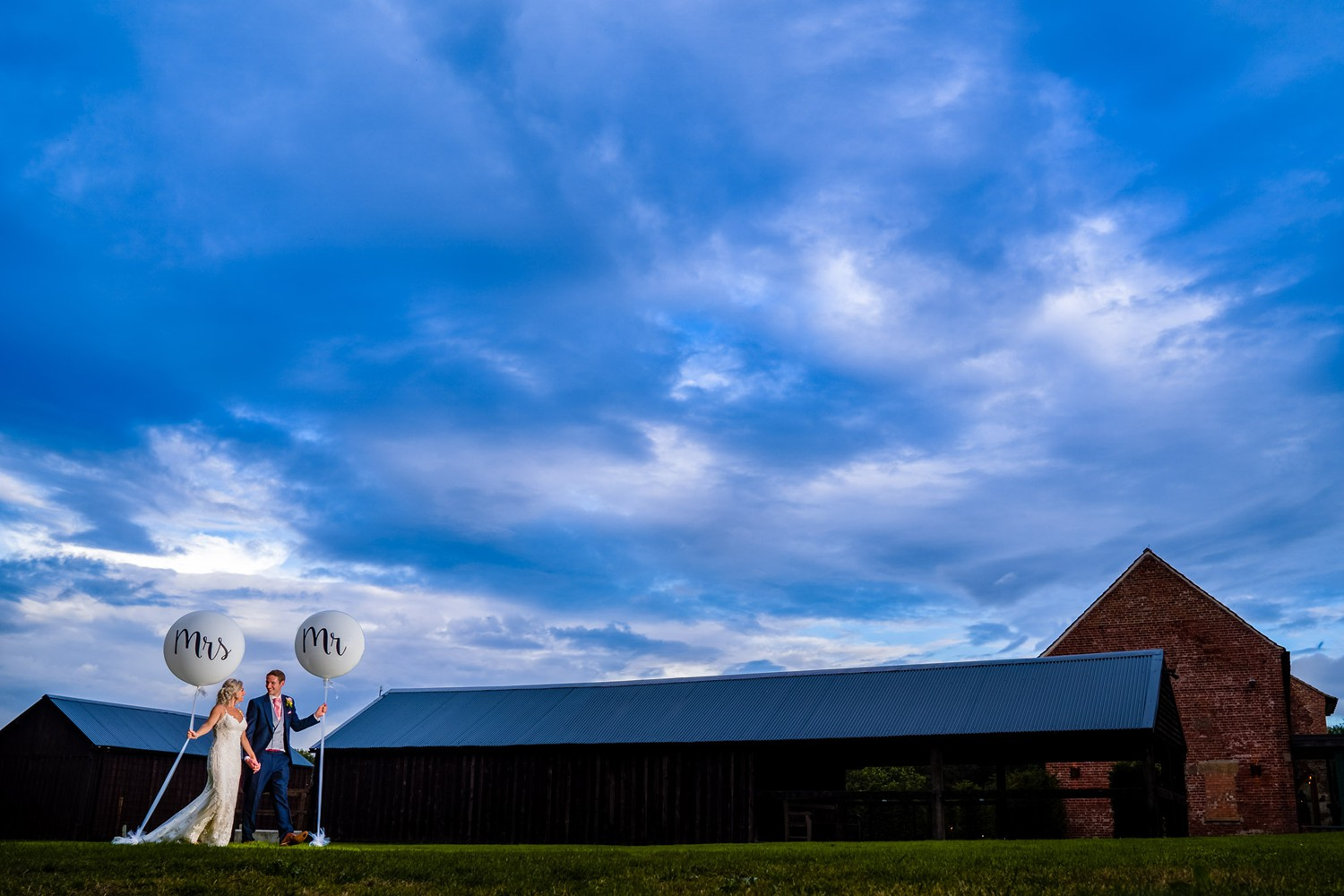 Bride & groom walking in the back gardens of Hazel Gap Barn holding giant Mr & Mrs balloon's with a dramatic blue sky