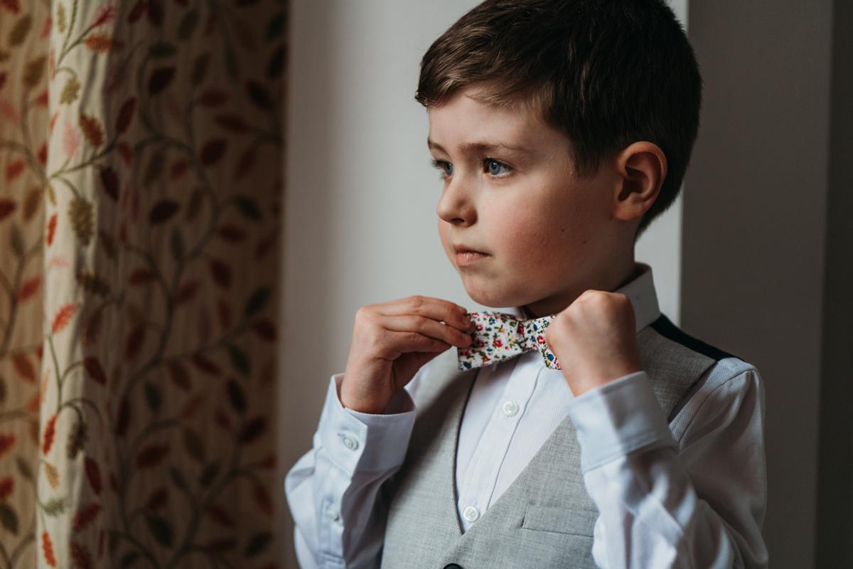 Page Boy adjusting his bow tie before his mum's wedding at Kelham Hall