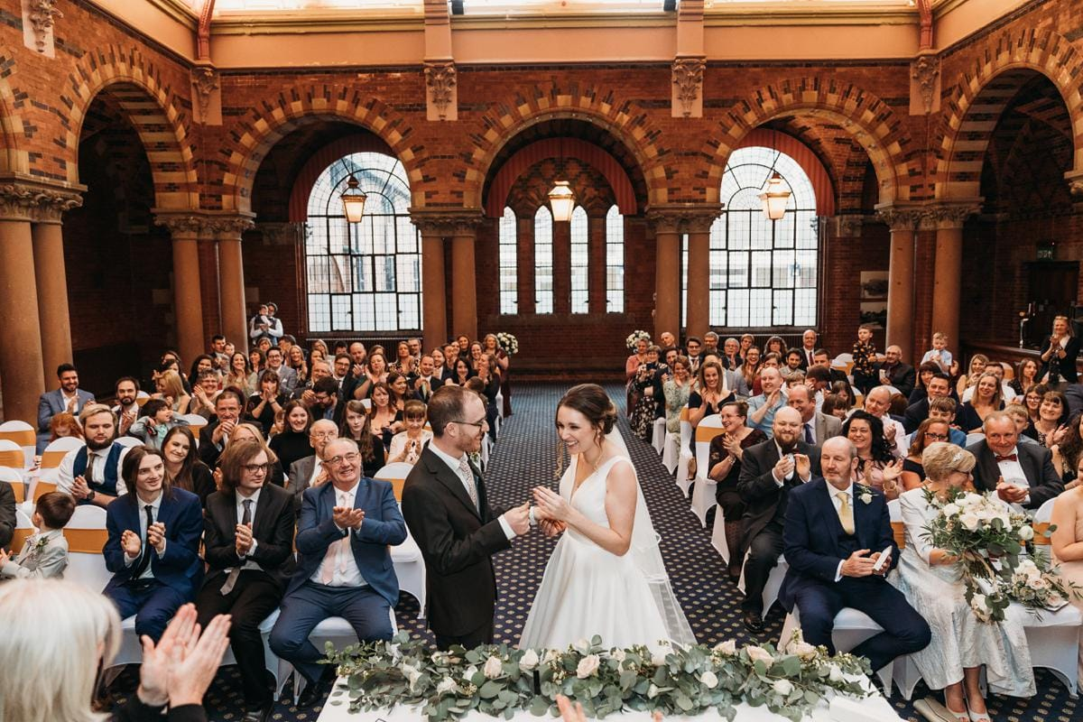 Bride & groom getting a round of applause by guests who are sat behind them after they exchanged wedding vows at their wedding at Kelham Hall