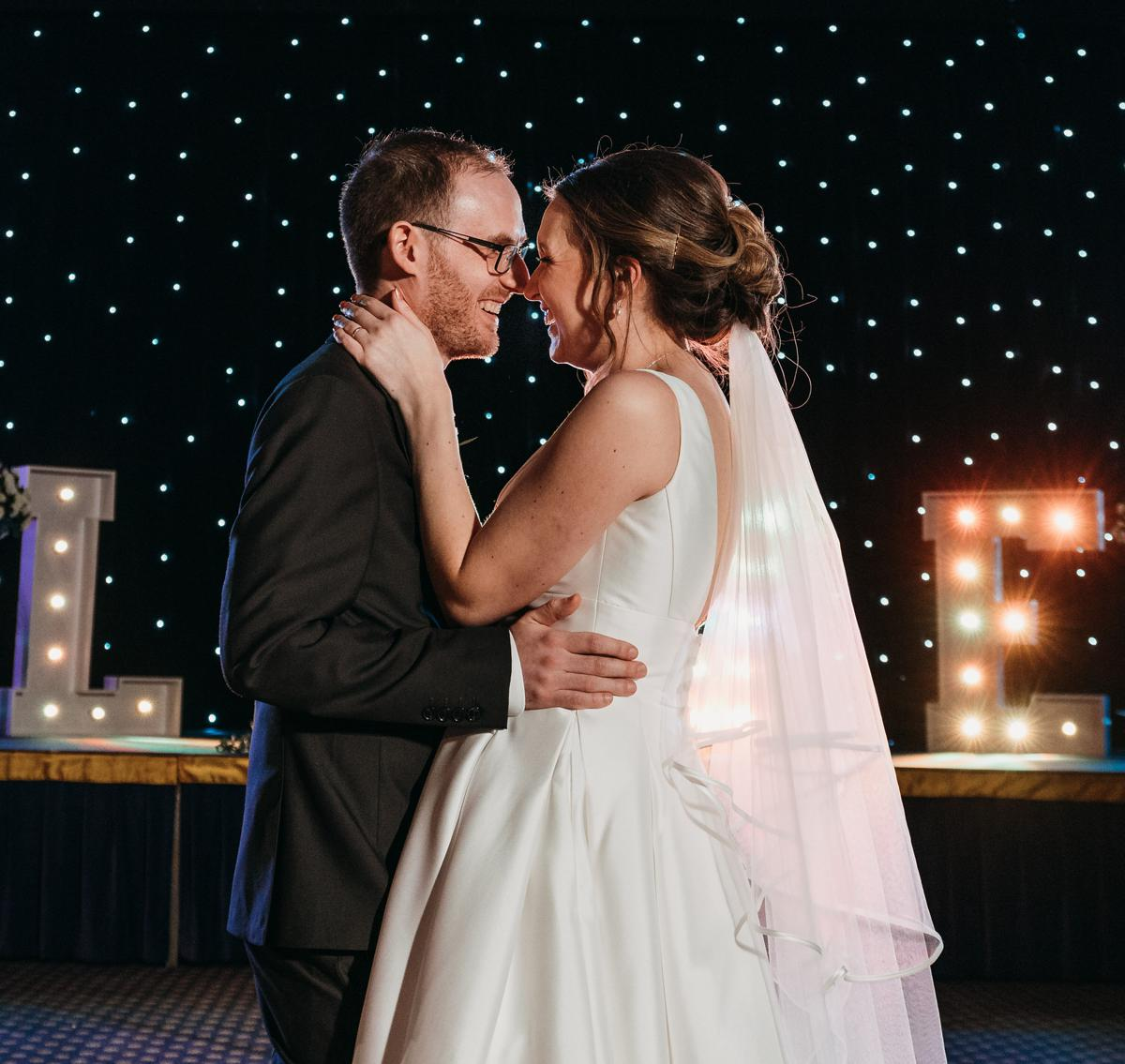 Bride and groom laughing with each other as they perform their first dance at their wedding at Kelham Hall