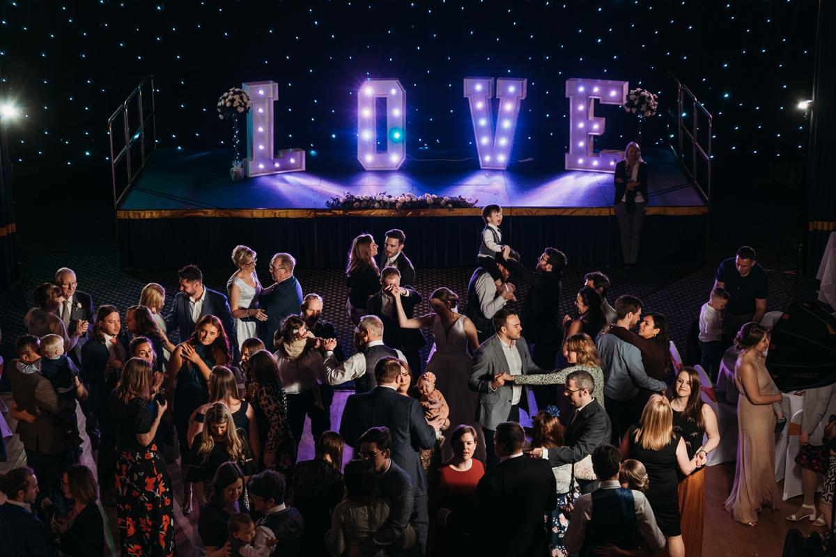 People dancing in the Great Hall at Kelham Hall with giant LOVE letters at the back of the room on the stage