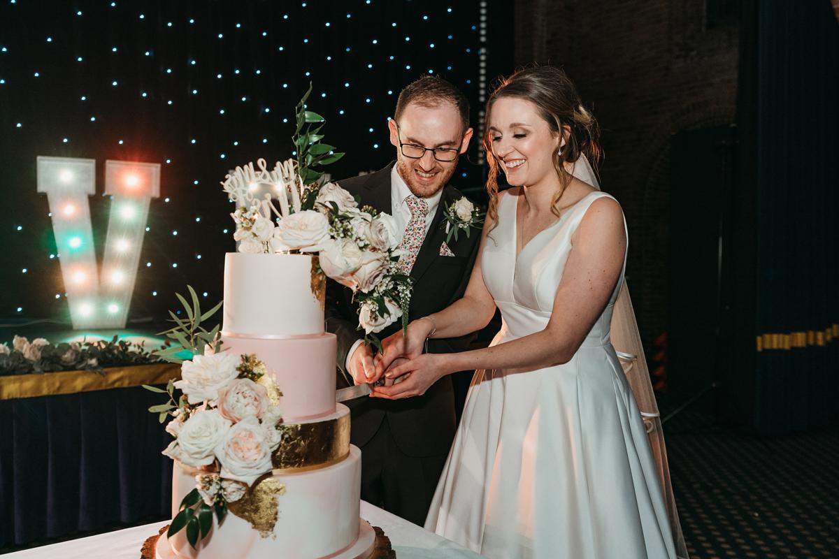 Cutting the wedding cake at Kelham Hall