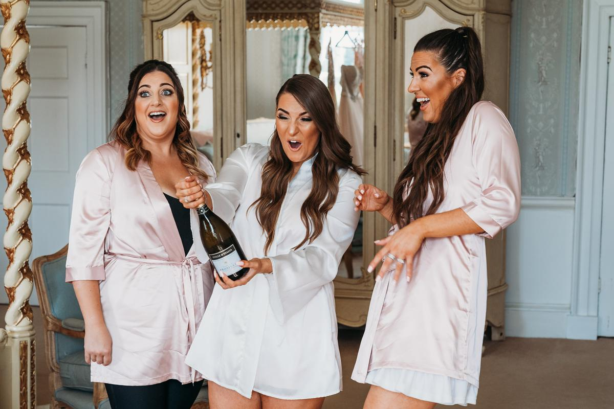 Norwood Park Wedding Photos of a bride surprised as she pops prosecco bottle with her bridesmaids
