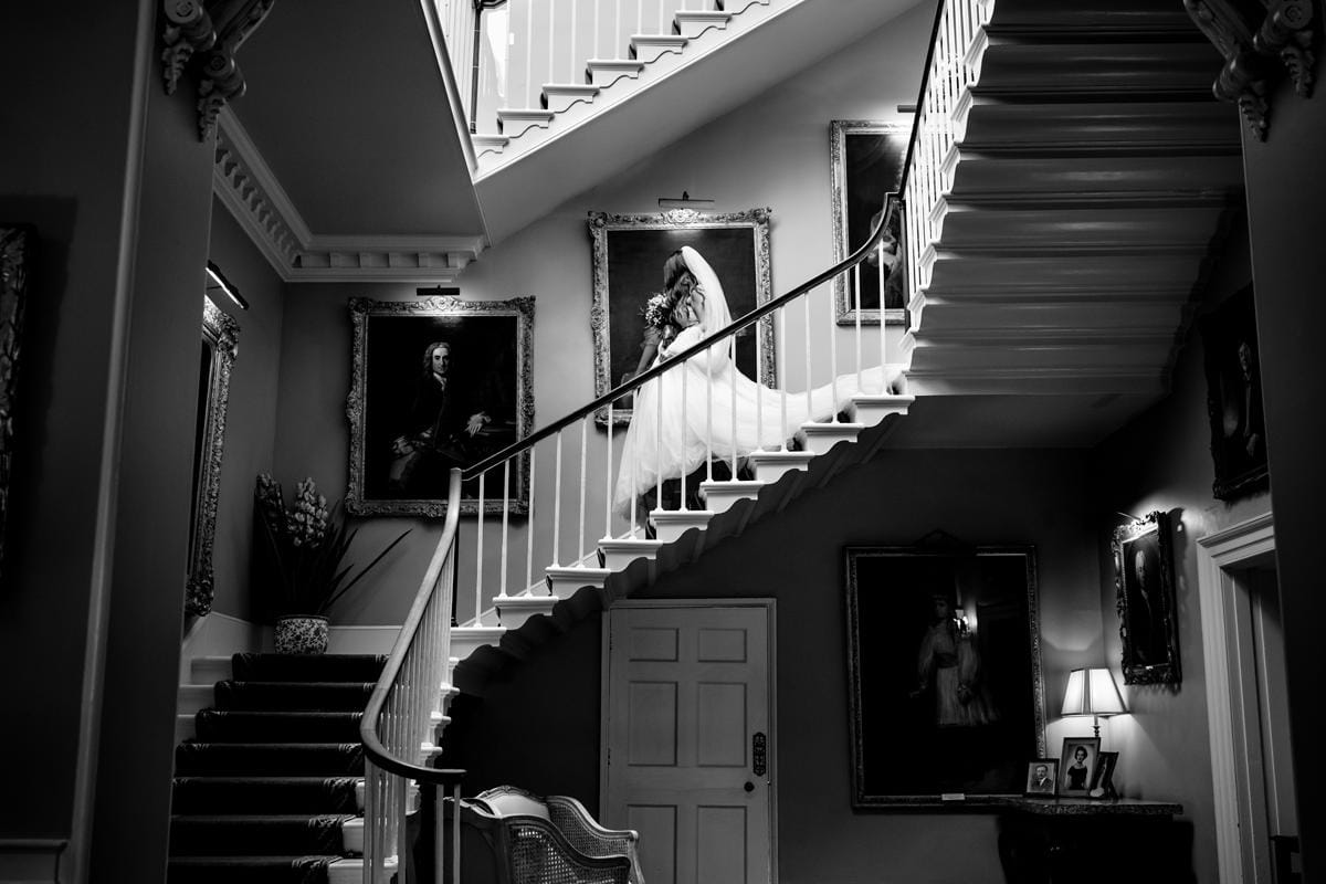Black and white photo of bride walking down the stairs at Norwood Park