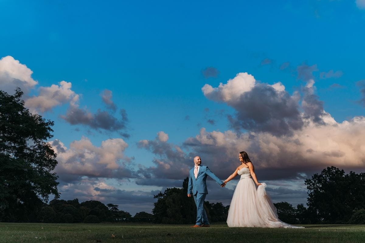 Groom walks in front of bride leading her by her hand as they walk across the gardens at Norwood Park with a beautiful blue sky at sunset