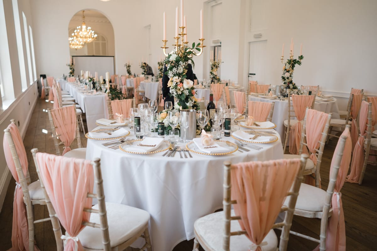 The Gallery room all set up for a wedding breakfast with tables decorated with candles and coral coloured chair covers and sashes
