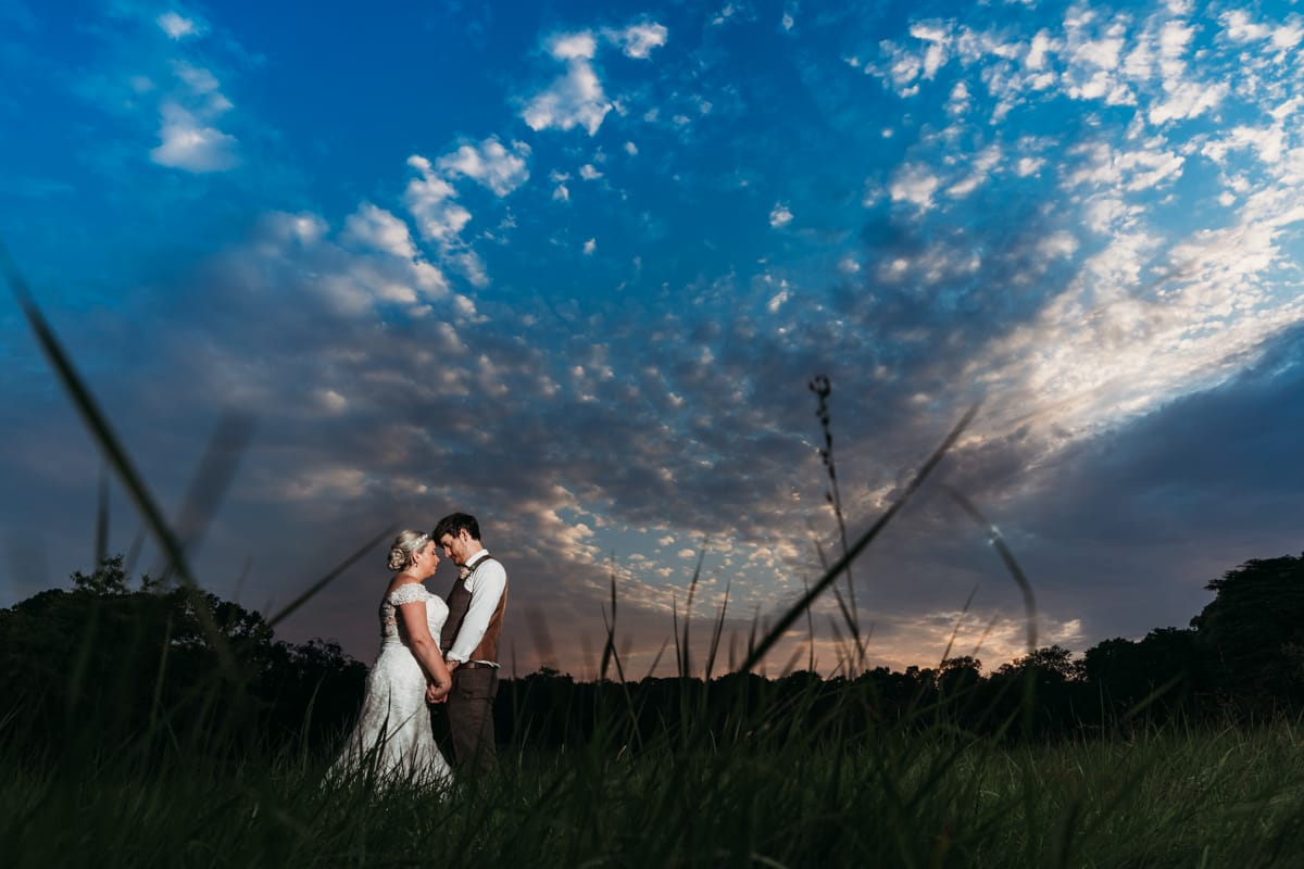 Sunset photo of bride & groom with Norwood Park in the background