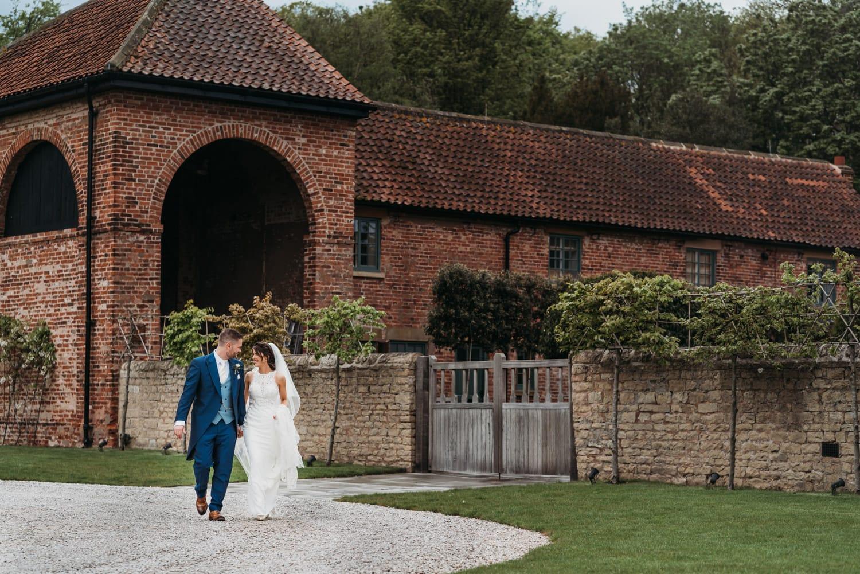 Bride & groom walking down the path at Hazel Gap Barn Nottingham