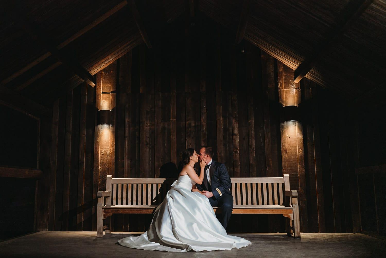 Bride & groom kiss sat on the bench at Hazel Gap Barn at night