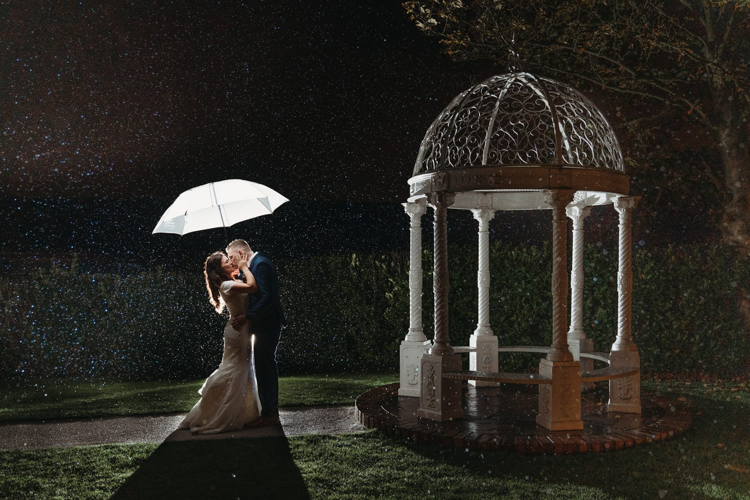 Raining photo of bride & groom outside Nottinghamshire Golf & Country Club