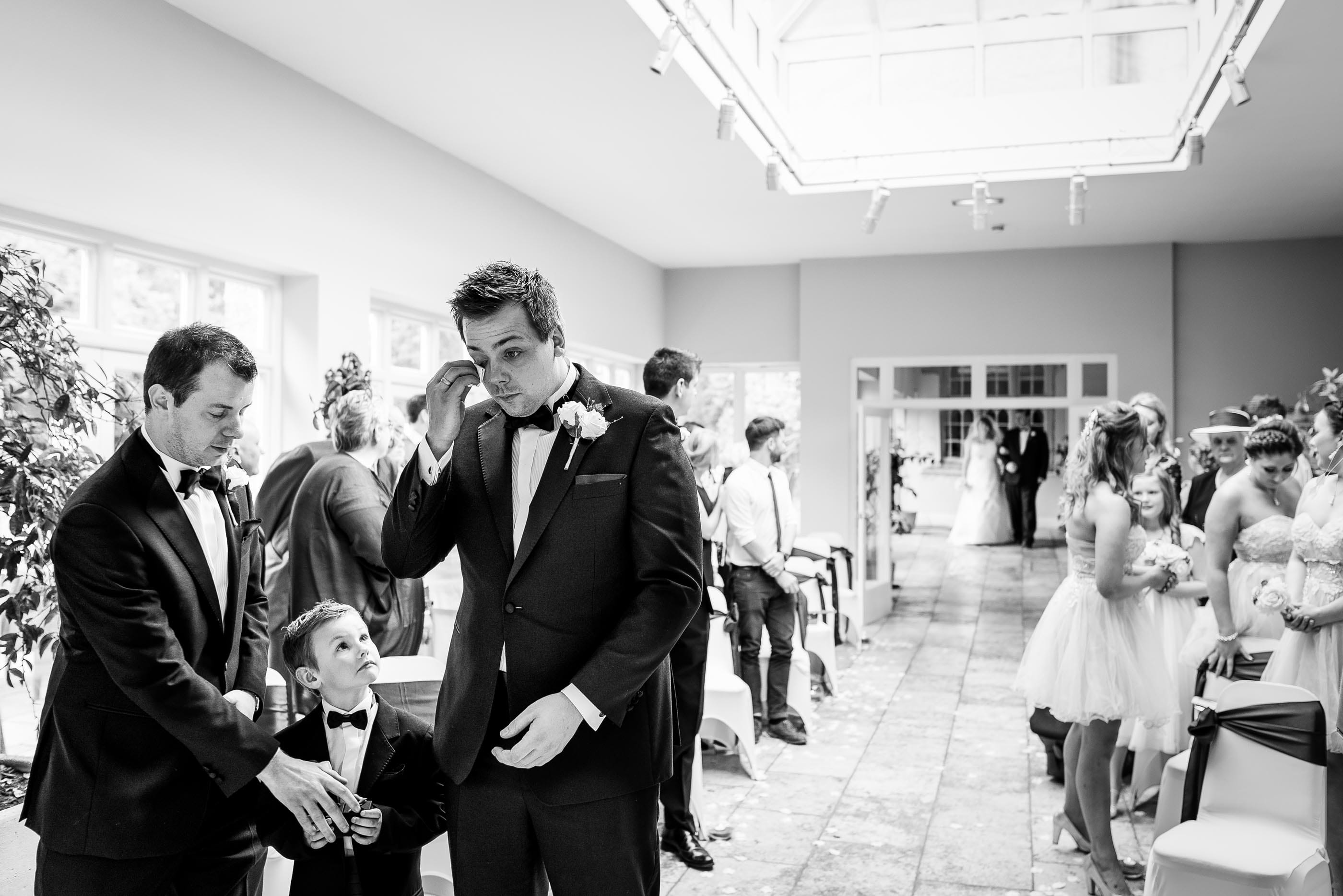 Groom wipes away a tear as soon watches. Just as bride walks down the aisle
