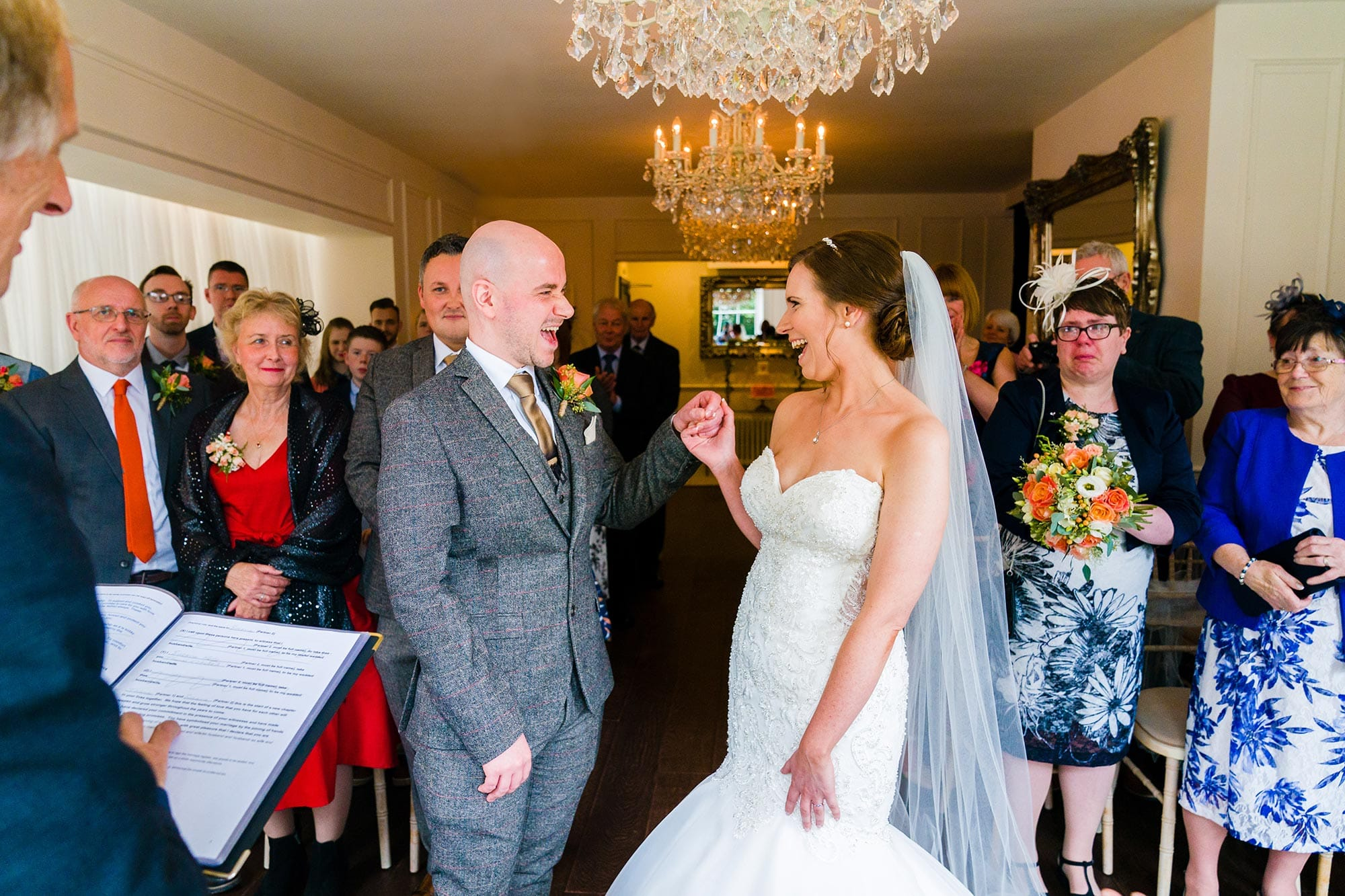 A wedding photo taken at Old Vicarage in Nottingham of the Bride and groom cheering just after the registrar prounounces them husband and wife, whilst their friends and family look on. Mother of bride's face is red from all the crying during the ceremony.
