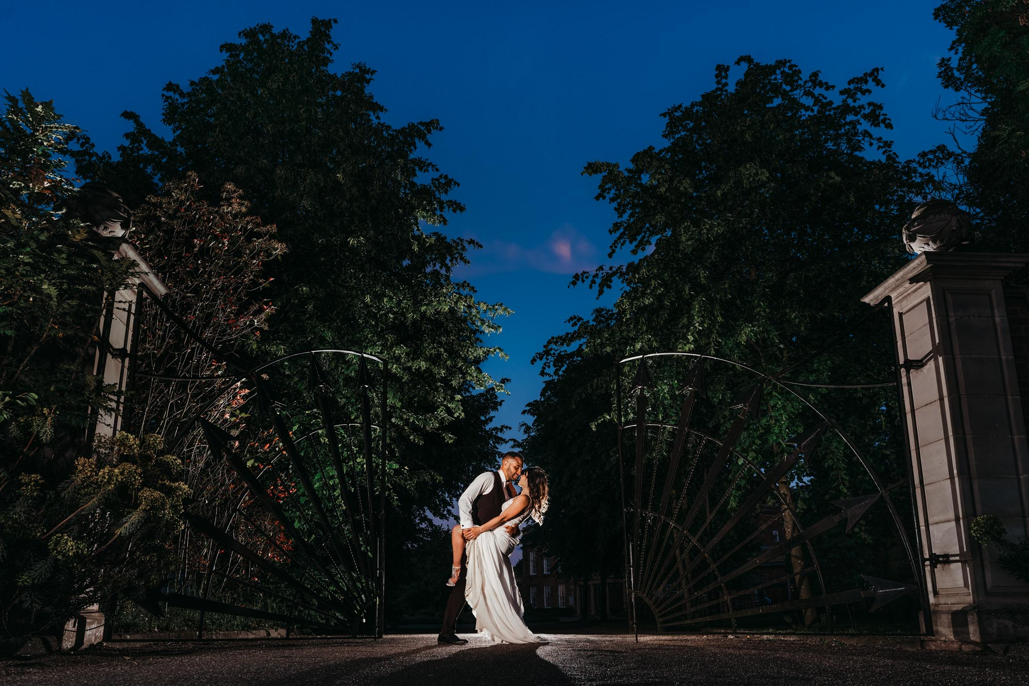 Wedding photograph of groom dipping the bride at the front gates outside Colwick Hall in Nottingham. Beautifully lit with a flash at the front so the sky is blue and the hall behind them.