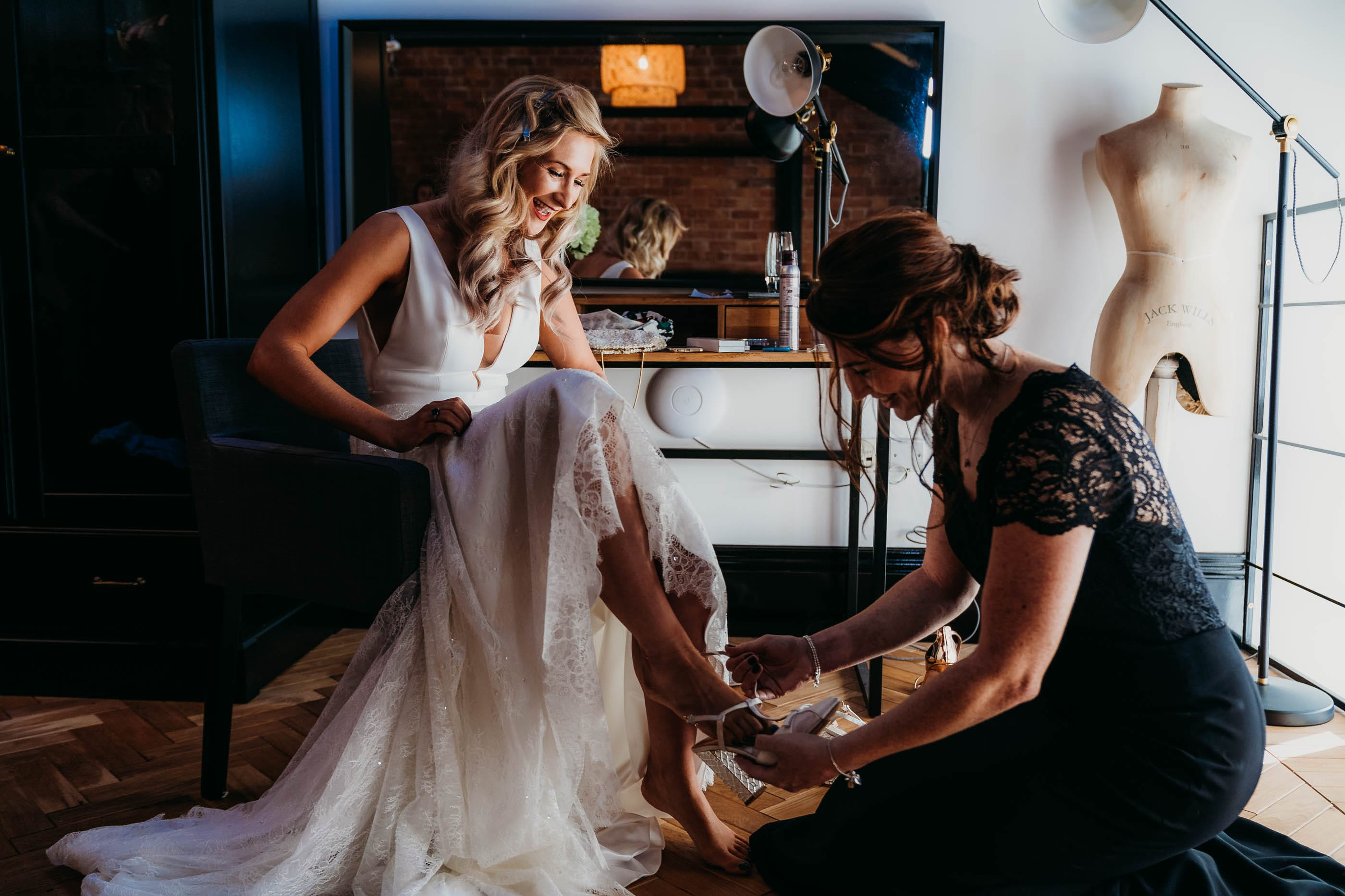 Bride putting on wedding shoes at Nottingham Wedding at Pumping House, Ollerton