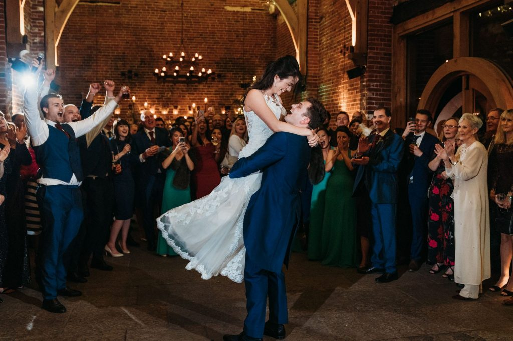 groom picks bride up during first dance for a spin. Guests look on clapping and cheering