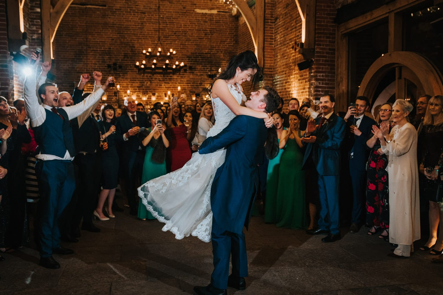 Groom lifts bride up for a spin during first dance at Hazel Gap Barn whilst guests cheer