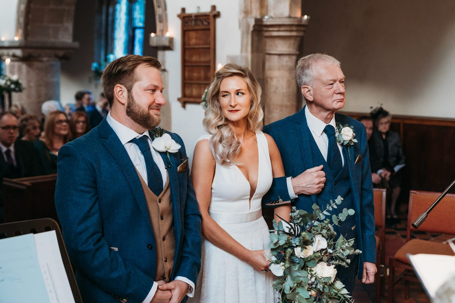 Bride gives her groom a reassuring wink as she reaches the top of the aisle at a church wedding