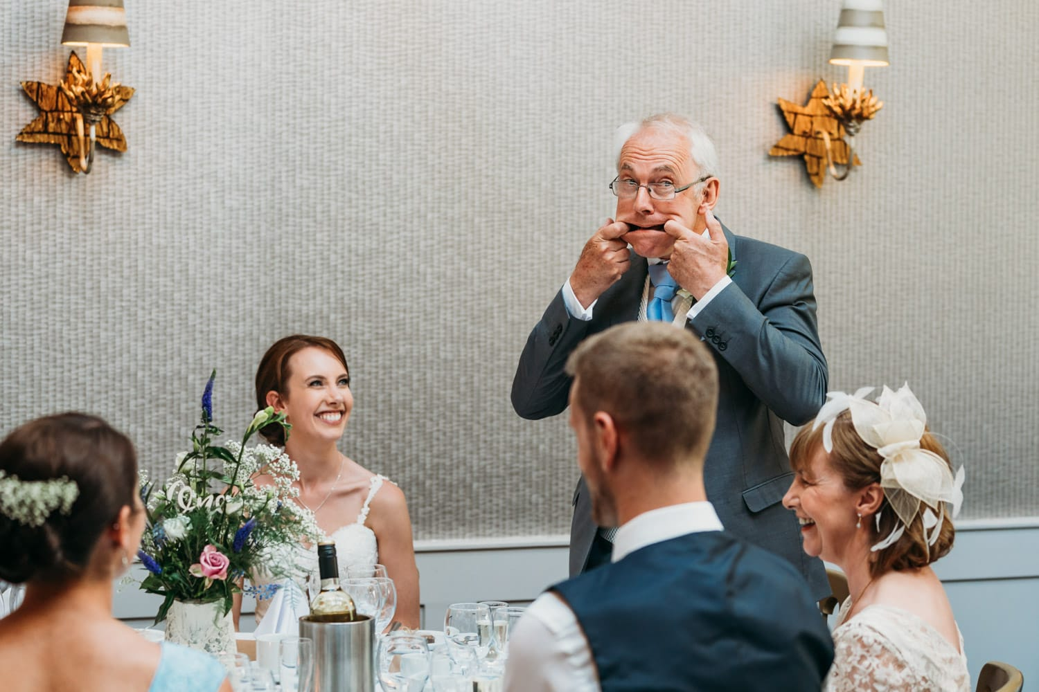 Father of bride pulls a funny face as he's delivering his wedding speech