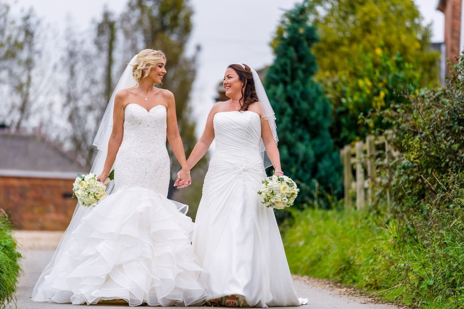 Two brides walking hand in hand at Swancar Farm