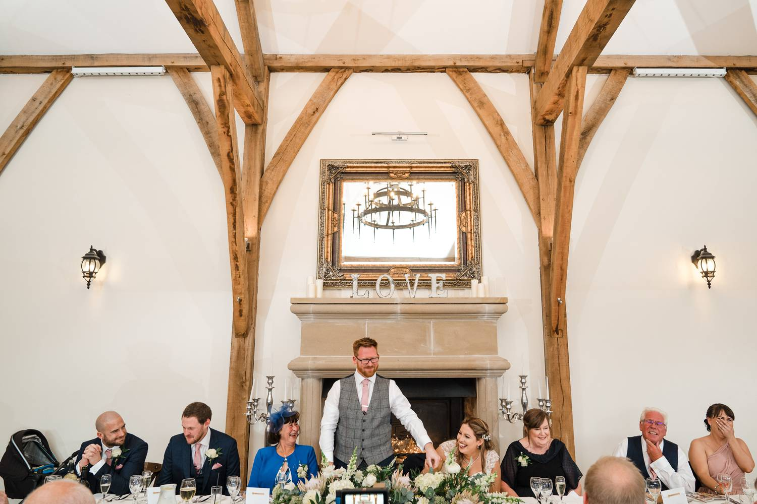 A wide photo showing all the wedding party sat at the top table at Swancar Farm during the groom's speech. The bride is laughing whilst the groom puts his hand on her shoulder. The maid of honour covers her mouth with laughter