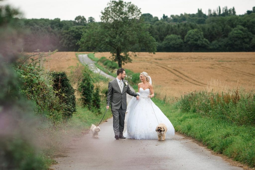 Bride & Groom walk up path at Swancar Farm