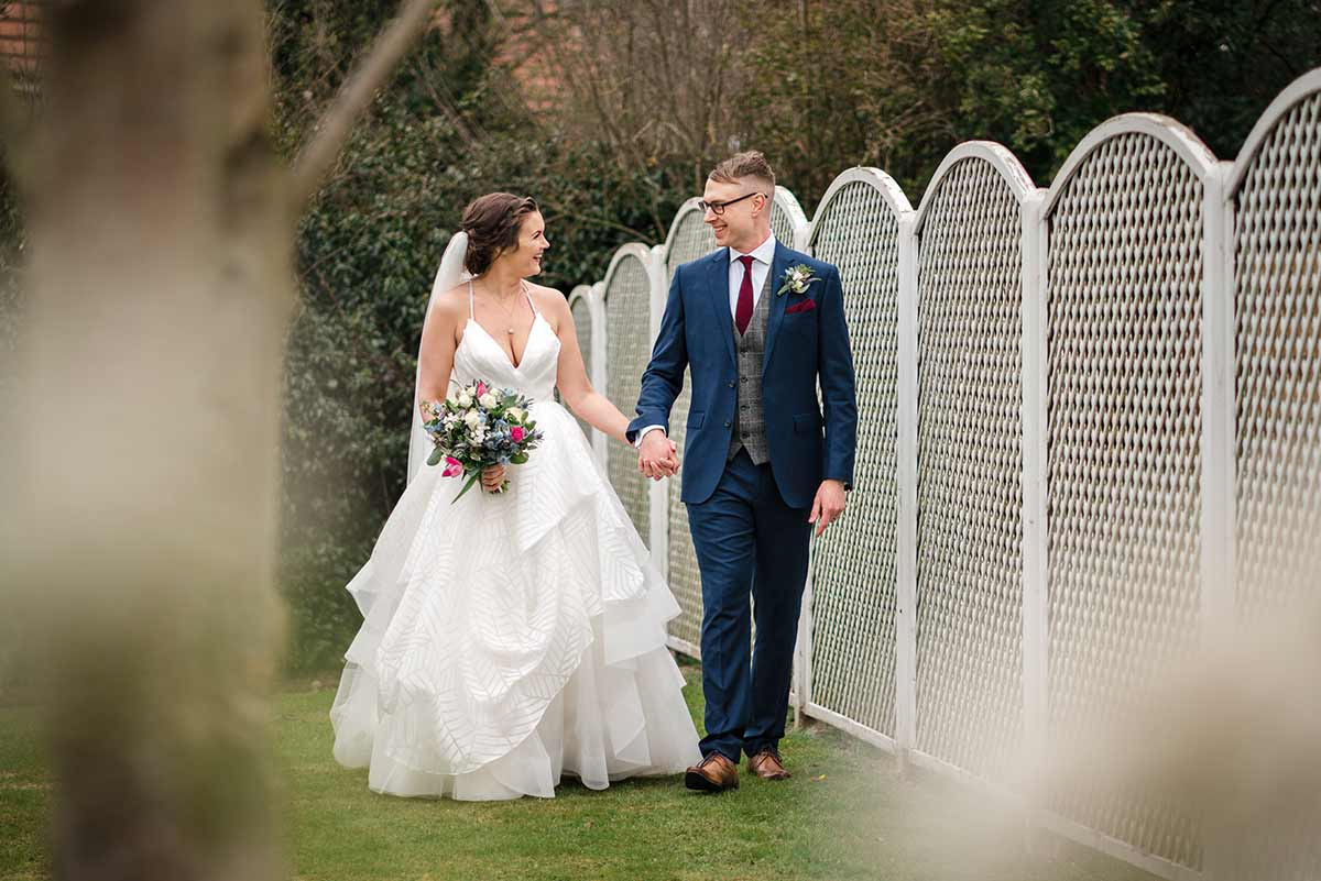 Bride & groom walking hand in hand at the Old Vicarage Boutique Hotel in Nottingham