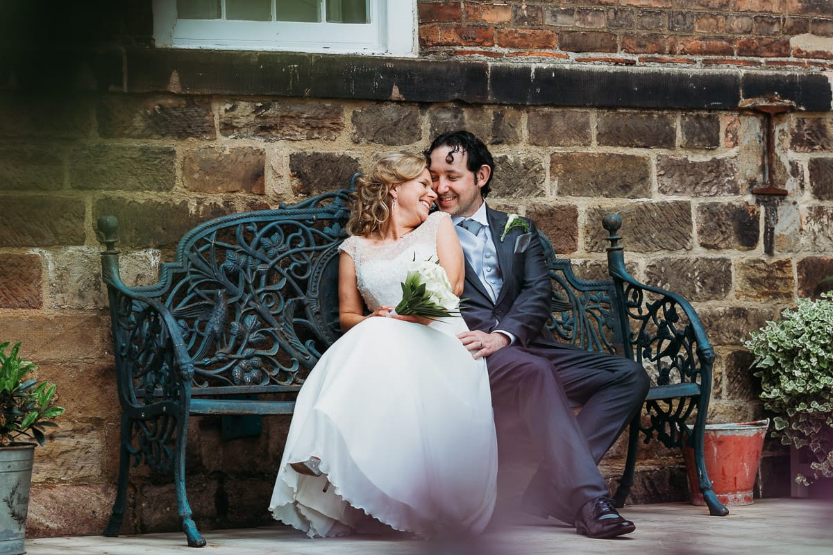 Bride cuddles up to the groom on a bench at The West Mill, Derby