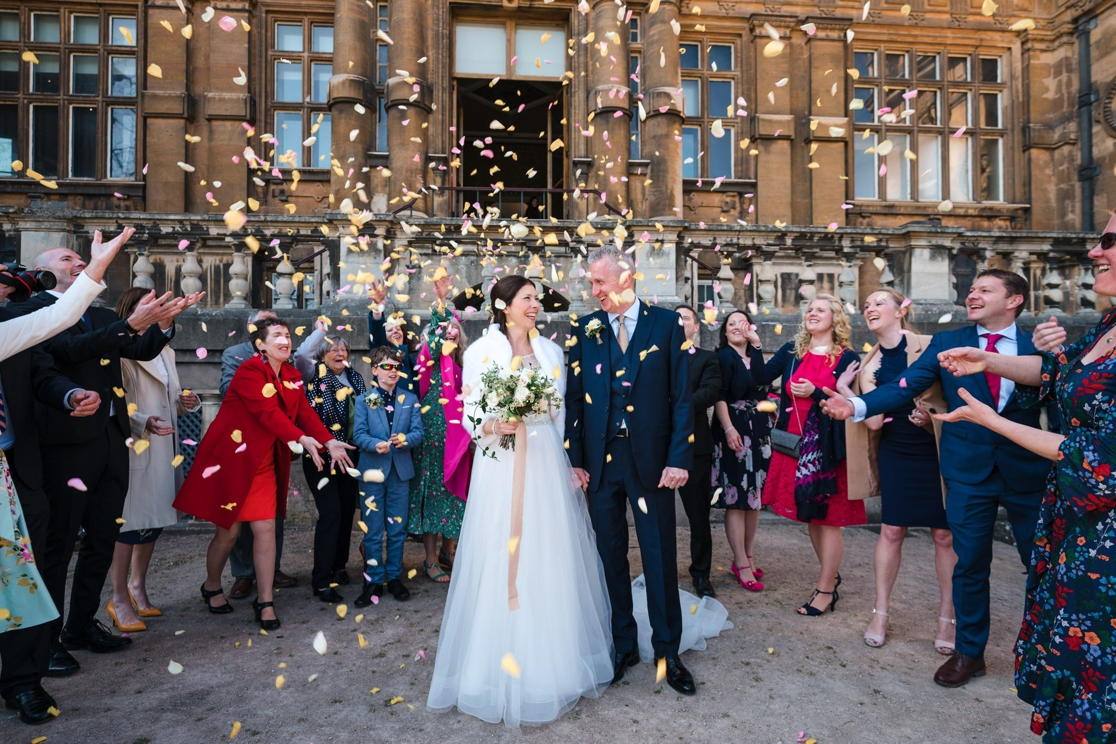 Guests throwing confetti over bride & groom outside Wollaton Hall in Nottingham
