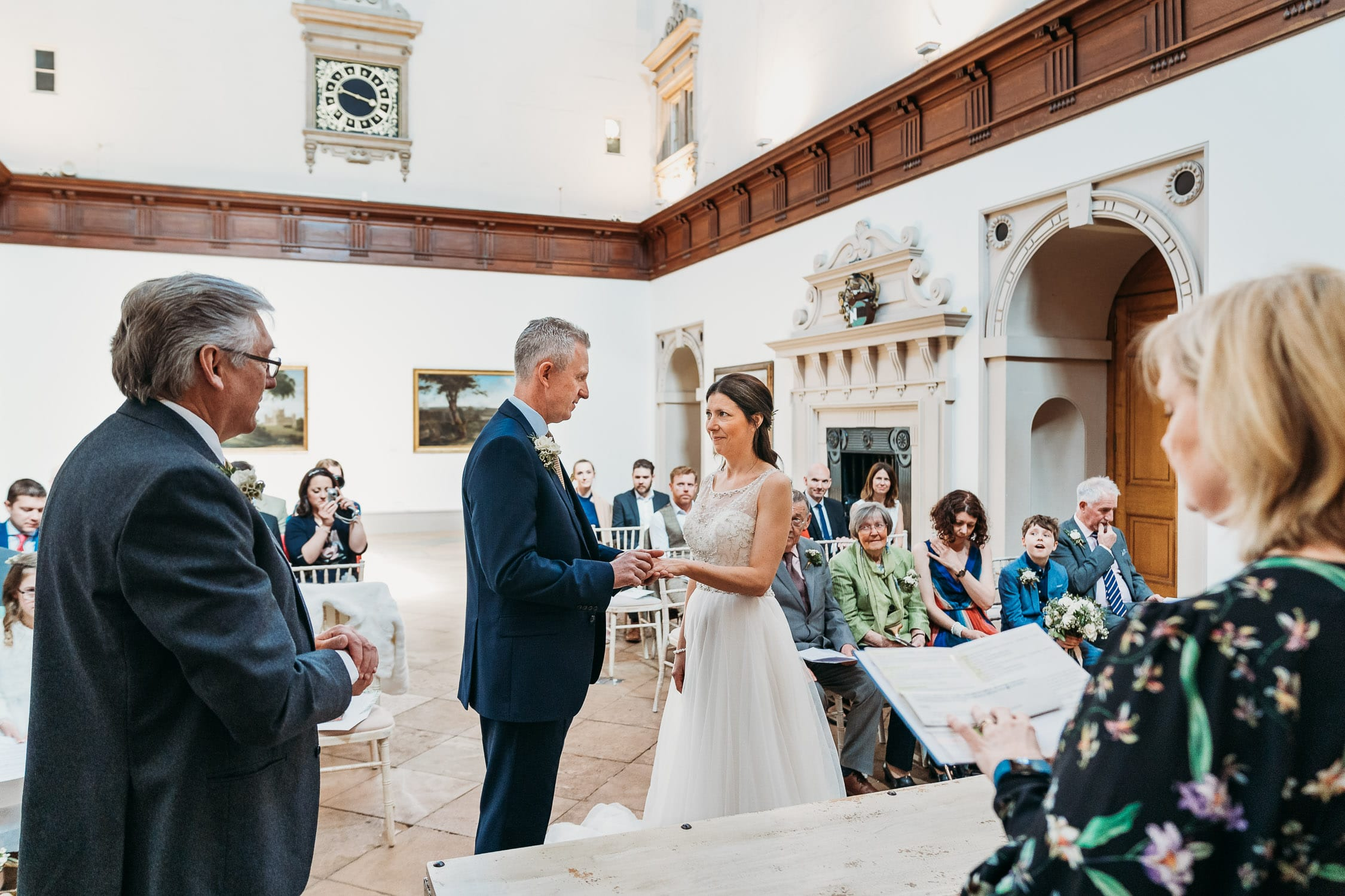 A photo of Bride and groom exchanging wedding rings during their wedding ceremony in the grand hall at Wollaton Hall Nottingham