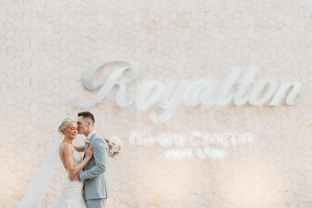 bride & groom photograph with the Royalton Riviera sign in the background at the hotel