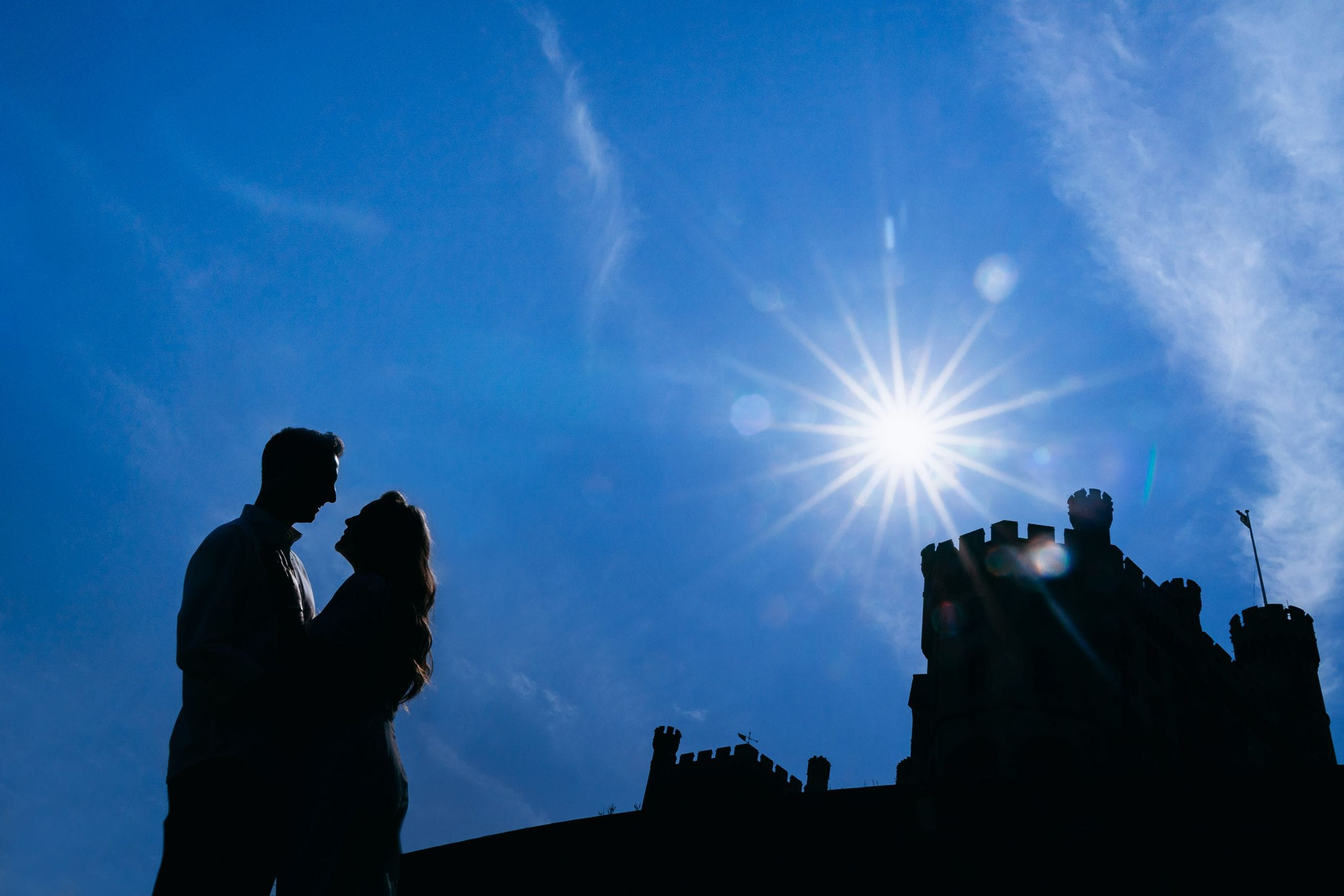 silhouette photograph of couple getting married with Belvoir Castle behind them