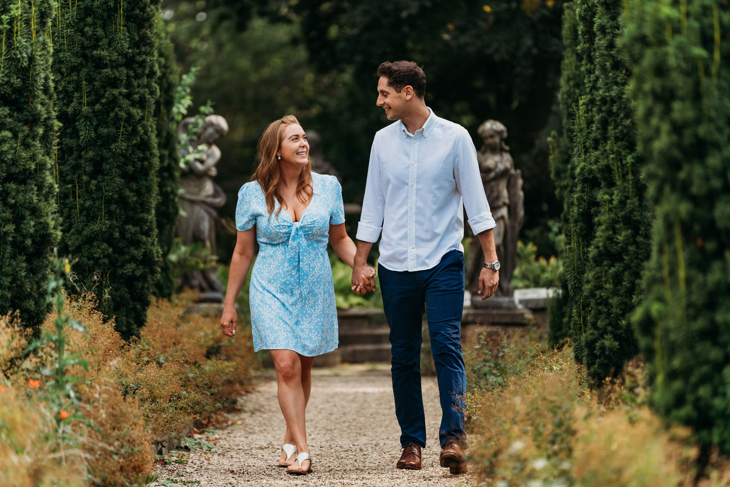 Photo of bride & groom who are getting married at Belvoir Castle walking in the rose garden