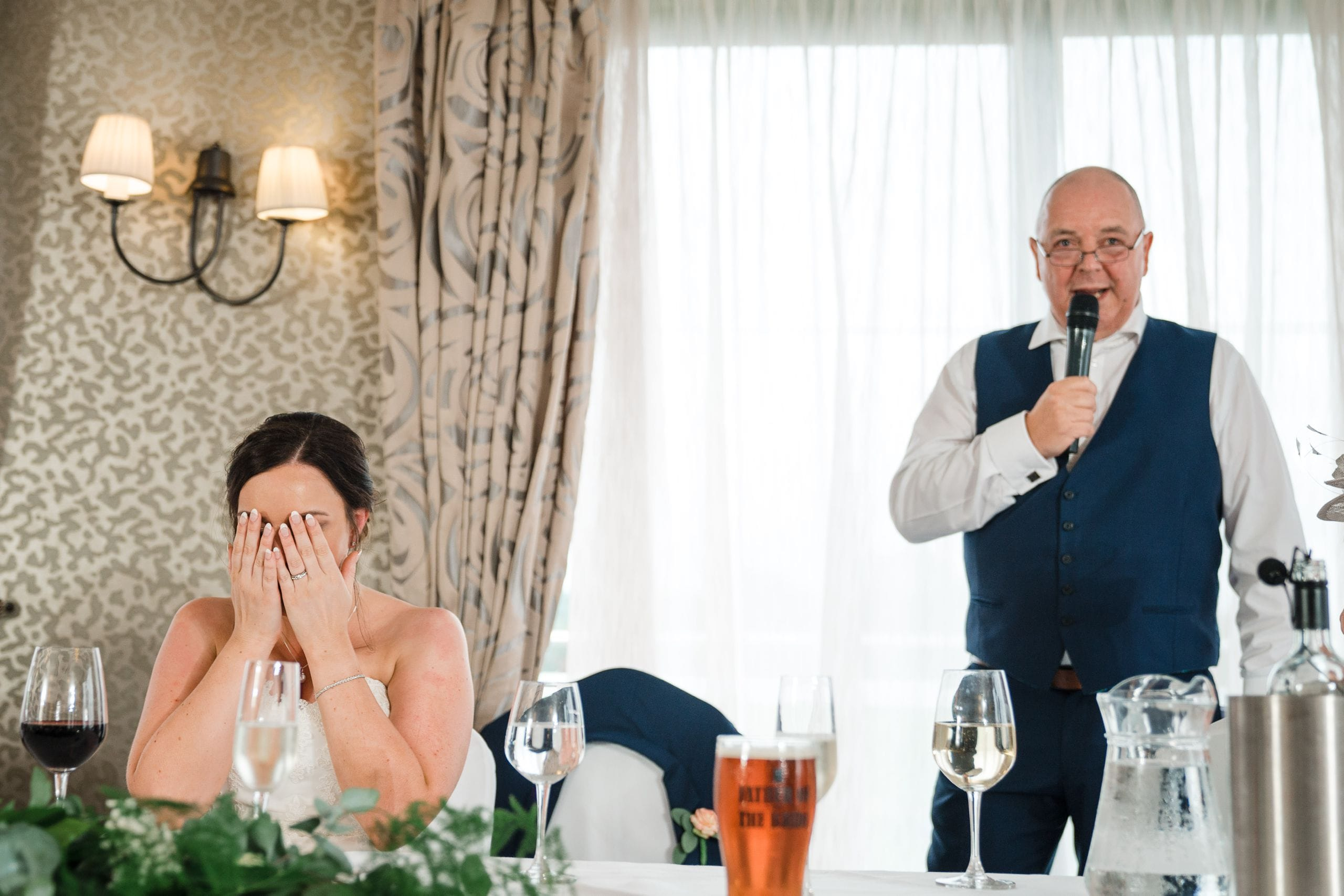 Bride covers face during Father of Bride speech