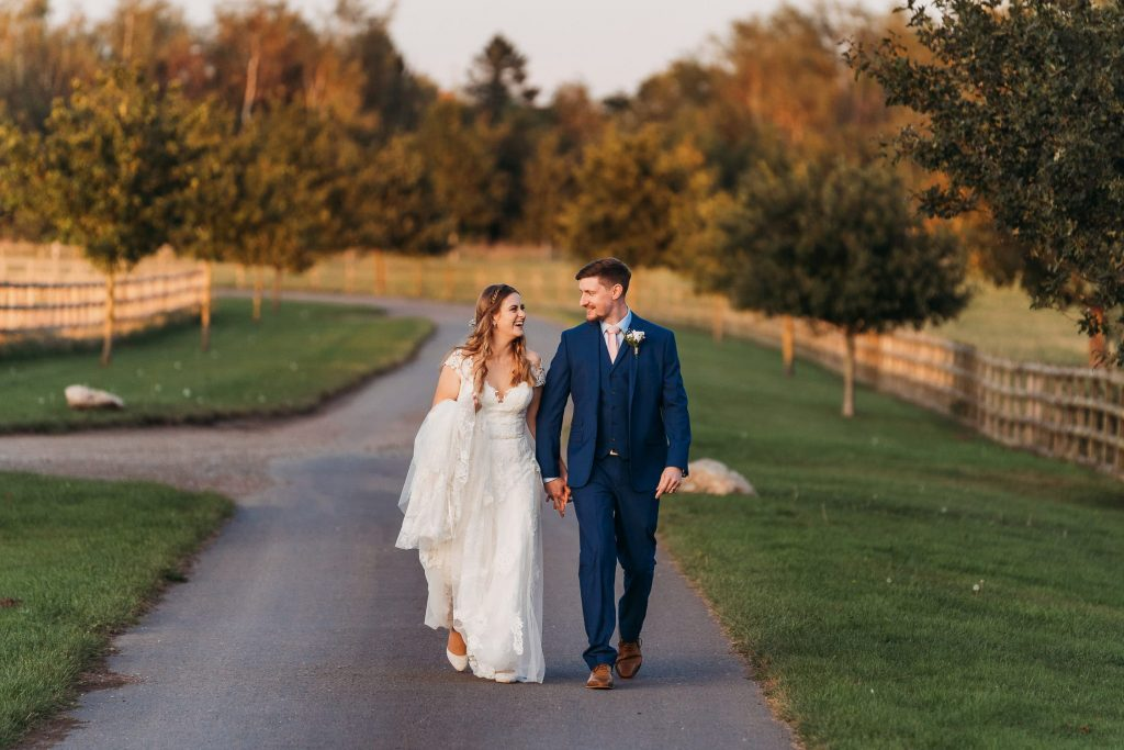 bride and groom walking back to venue after their photo session at Mythe Barn