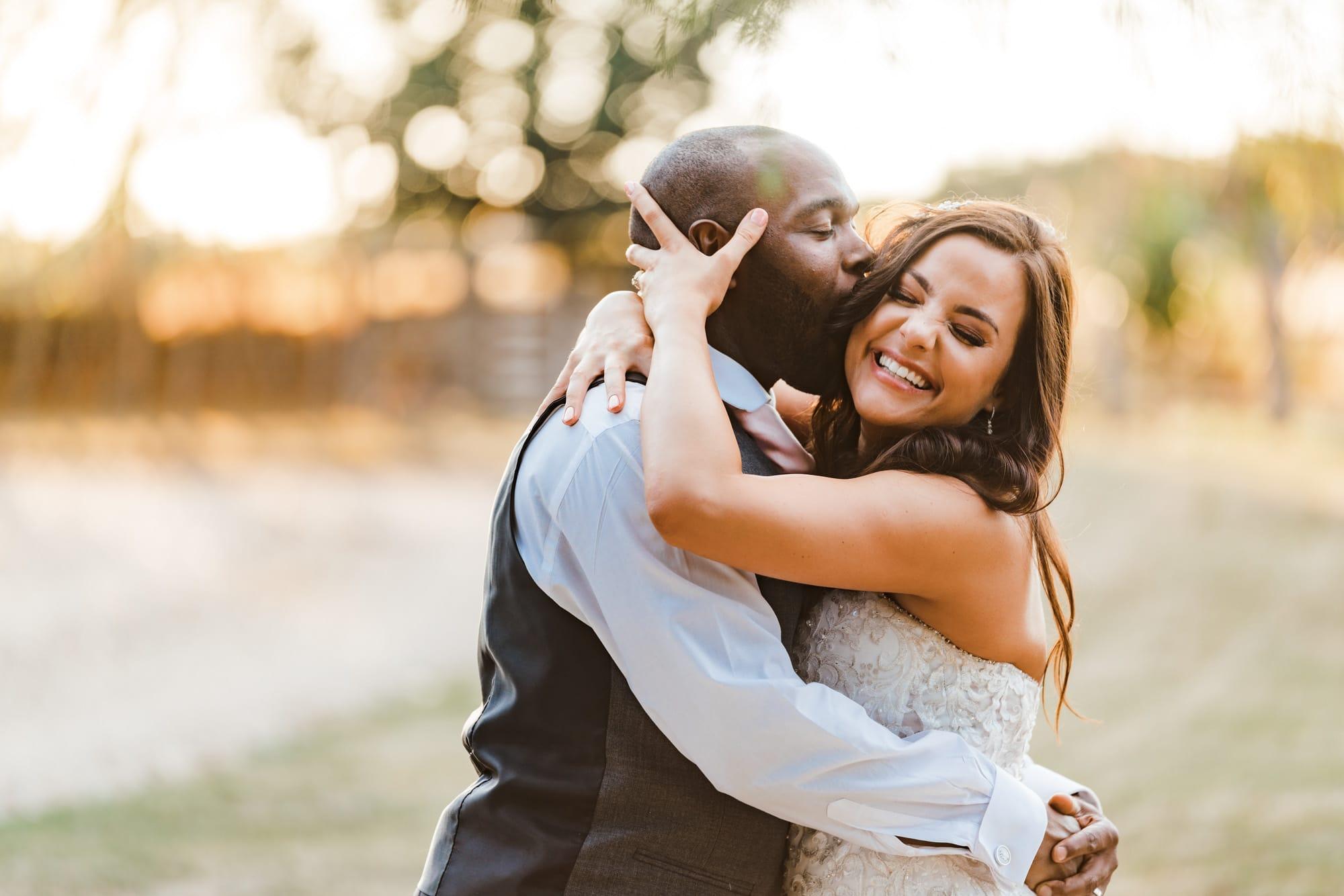 Bride laughing as groom kisses her