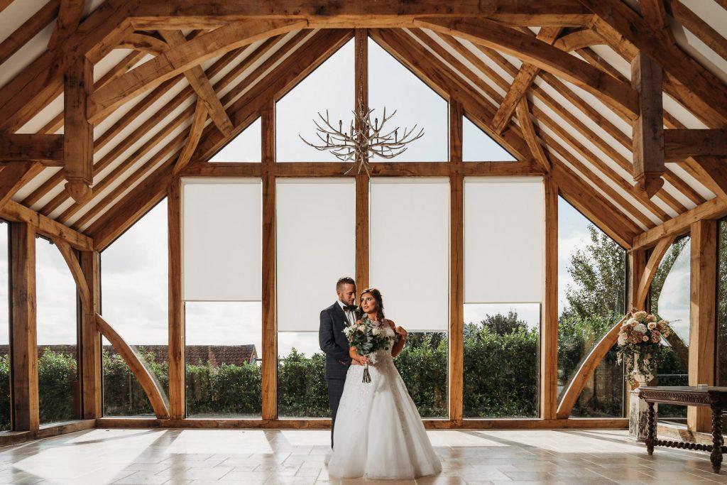 Wedding photo of bride & groom in the Glass Barn at Swancar Farm